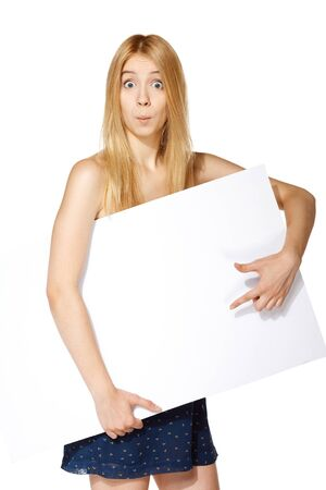 astonished: Funny image of surprised teenage girl holding white board under her hand and pointing at it, over white background