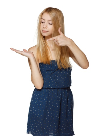 Girl holding blank copy space on her open palm - space for your text or product, and pointing at it, over white background photo