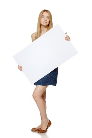 Young female wearing blue sundress standing in full length and holding blank banner, over white background photo