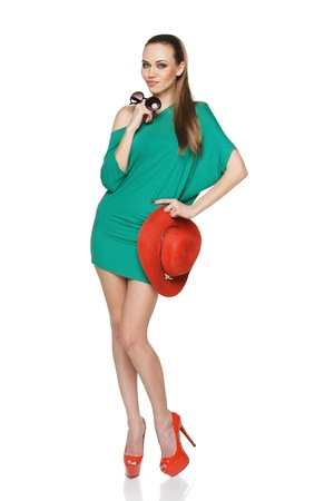 Smiling fashion summer woman in full length wearing green dress and high heels red shoes holding straw hat and sunglasses Stock Photo