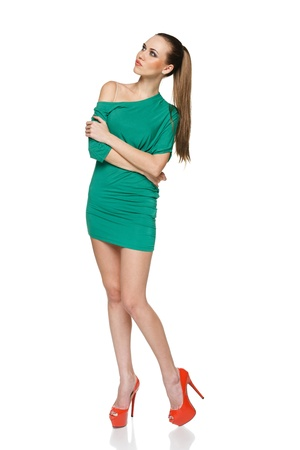 Summer woman in full length wearing green dress and high heels red shoes looking up at copy space  Isolated on white background photo
