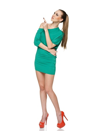 Summer woman in full length wearing green dress and high heels red shoes looking and pointing up at copy space  Isolated on white background photo