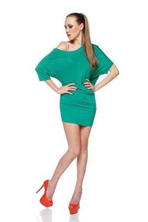 Woman in full length wearing green dress and high heels red shoes posing with hands on hips  Isolated on white background