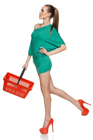 Fashion woman in full length wearing green dress and high heels red shoesholding empty shopping basket  Isolated on white background photo