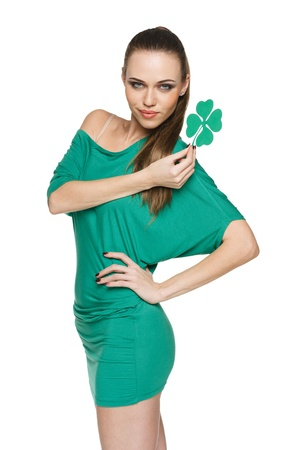 Woman wearing green dress showing artificial green shamrock leaf against white  background photo