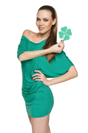 saint patrick s day: Woman wearing green dress showing artificial green shamrock leaf against white  background