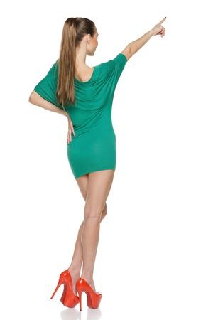 Vue arrière de la mince jeune femme en mini robe verte en pleine longueur pointant vers le haut, sur fond blanc