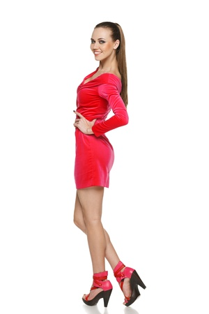 Flirtatious young woman in pink dress standing in full length against white background Stock Photo