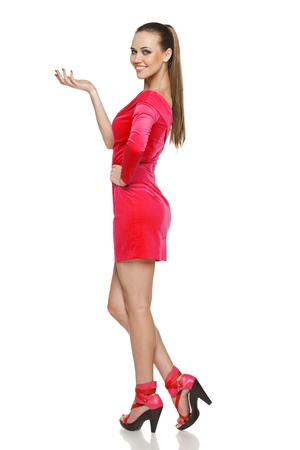 Coqueta joven vestida de rosa de pie en toda su longitud y mostrando copia en blanco, contra el fondo blanco. Foto de archivo