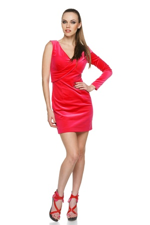Full length of young woman wearing pink cocktail dress posing with hand on hip against white background
