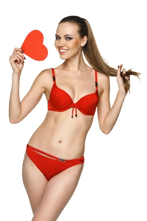 Happy young woman in red bikini showing heart shape against white background