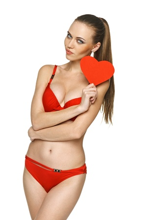 cheeful: Woman in red bikini showing heart shape against white background