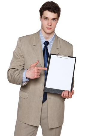 Young serious businessman holding blank whiteboard, pointing at it, over white background photo