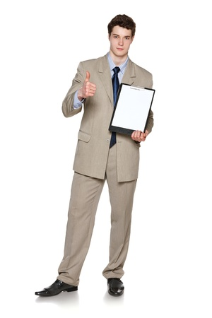 Full length of young businessman holding blank whiteboard showing thumb up gesture, over white background photo
