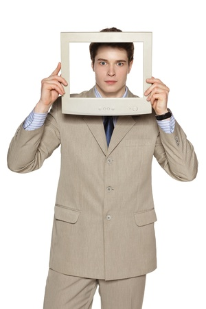Scared young businessman in beige suit looking through the TV   computer screen frame over white background photo