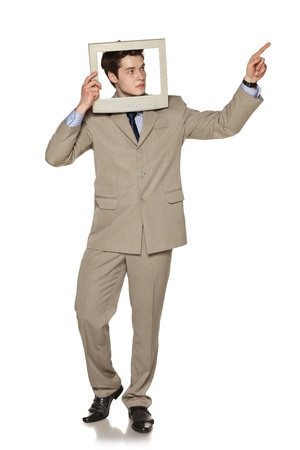 Young businessman in beige suit standing in full length looking through the TV   computer screen frame and pointing to the side, against white background photo