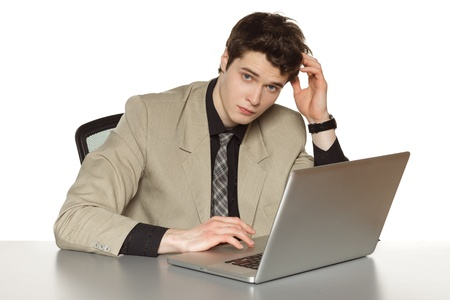 Youn business man sitting at the table with laptop, scratching his head, over white background photo