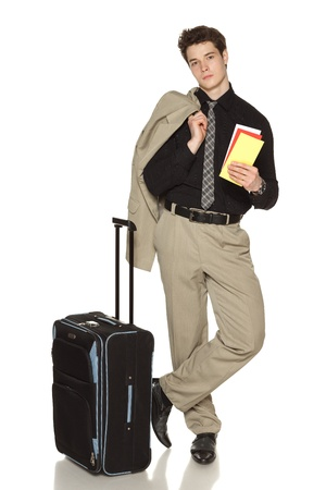 business traveller: Business travel  Young businessman standing with travel case and holding tickets in full length, over white background