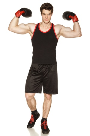 Young male wearing boxing gloves showing his muscles against white background
