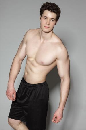 niño sin camisa: Apuesto joven deportes muscular en el fondo gris