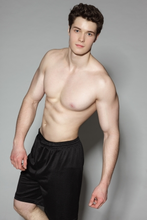 Handsome young muscular sports man on gray background photo