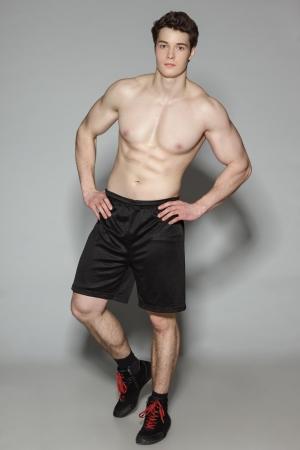 アスレチック青年が灰色の背景でフルの長さで上半身裸に立って