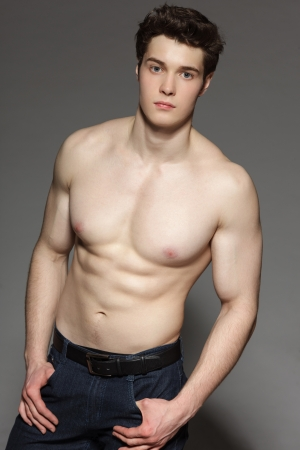 Gorgeous young man with bare torso gazing at the camera with hands in pockets, over gray background