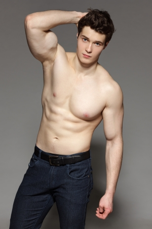 Sexy young man with bare torso gazing at the camera with hand on his head, over gray background