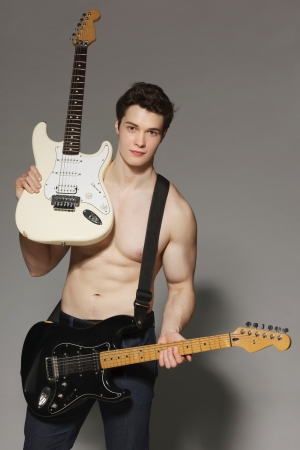 shirtless male: Smiling young muscular man with bare torso handing two electric guitars, over gray background