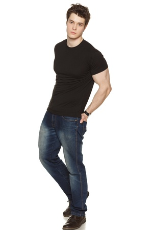 tshirts: Full length portrait of a casually-dressed young man with his hands in his rear pockets over white background Stock Photo