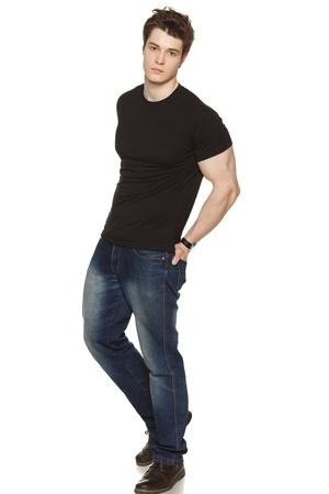 Portrait en pied d'un jeune homme en passant habillé avec ses mains dans ses poches arrière sur fond blanc