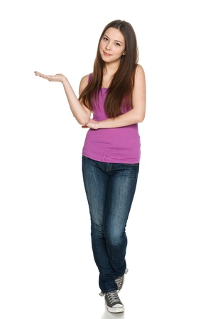 casually: Lovely teen girl in full length standing casually and holding blank copy space at her palm, looking at copy space, against white background