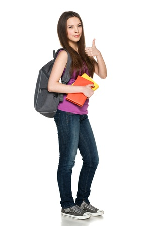 Smiling teen girl wearing a backpack and holding books showing thumb up, over white background photo