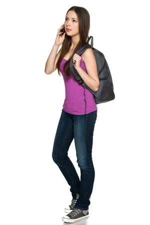 Full legnth of young female with backpack talking on cellphone while looking away, against white background photo