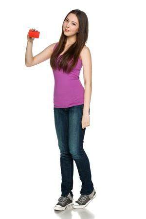 気軽に立っていると、白い背景の空白のクレジット カードを保持している完全な長さで素敵な十代の少女