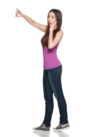 Surprised young teen female in full length pointing to the side, against white background photo