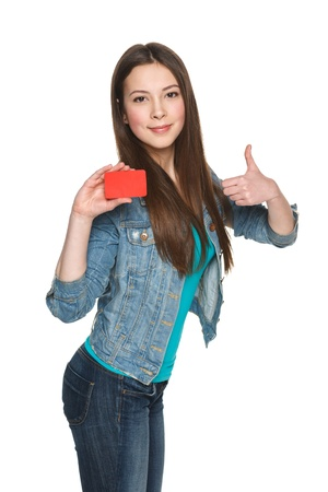 Young teen female showing blank credit card and gesturing thumb up against white background photo