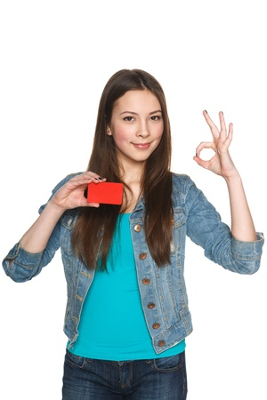 Young teen female showing blank credit card and gesturing OK against white background photo