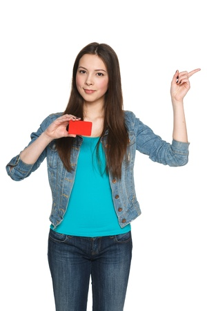 Young teen female holding blank credit card and pointing to the side at blank copy space against white background photo