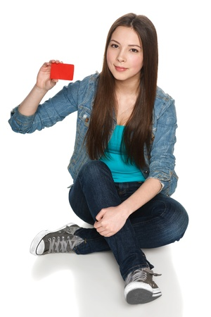 Young teen female sitting on floor showing blank credit card, isolated on white photo