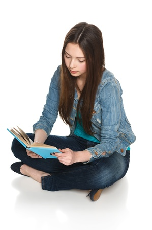 Young teen female student sitting on floor reading a book, isolated on white photo