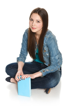 Young smiling relaxed female student sitting on floor with a book, isolated on white photo