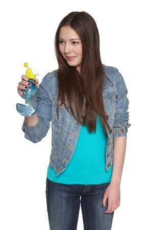 fregando: Sonriente mujer joven que apunta limpieza botella de spray a la cara, sobre fondo blanco
