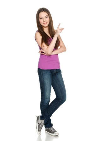 casually: Lovely teen girl in full length standing casually and pointing to the side at blank copy space, against white background