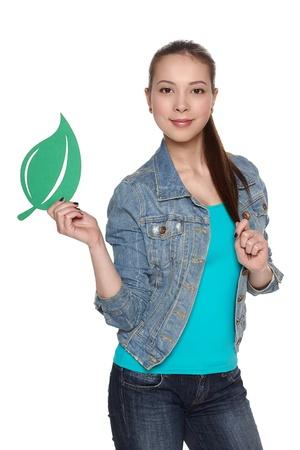 Casual denim teen female holding green leaf symbol against white background Stock Photo - 20499102