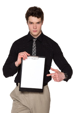 Young businessman holding blank clipboard , pointing at it, looking at camera with severe glance, over white background photo