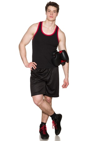 Full length of young boxer standing with gloves under his hand over white background photo