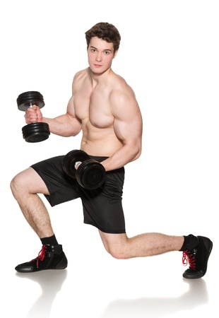 shirtless male: Muscular young man in full length training with dumbbells over white