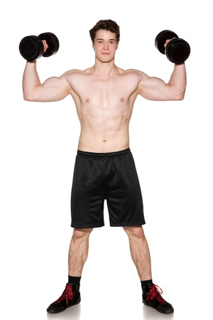 Muscular young man in full length lifting a dumbbell over white photo