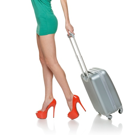 Side view of woman legs walking with a suitcase on the white background